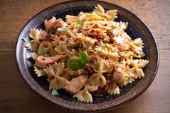Pasta with chicken, sun dried tomatoes and basil in creamy mozzarella sauce in bowl on wooden table. Horizontal Royalty Free Stock Photography