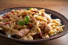 Pasta with chicken, sun dried tomatoes and basil in creamy mozzarella sauce in bowl on wooden table. Horizontal Stock Image