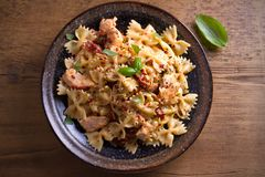 Pasta with chicken, sun dried tomatoes and basil in creamy mozzarella sauce in bowl on wooden table. Overhead, horizontal Stock Photo