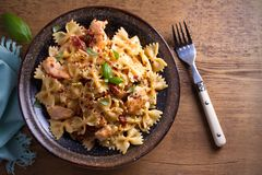 Pasta with chicken, sun dried tomatoes and basil in creamy mozzarella sauce in bowl on wooden table. Overhead, horizontal Royalty Free Stock Photos