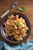 Pasta with chicken, sun dried tomatoes and basil in creamy mozzarella sauce in bowl on wooden table. Overhead, vertical Stock Images