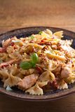 Pasta with chicken, sun dried tomatoes and basil in creamy mozzarella sauce in bowl on wooden table. Vertical Royalty Free Stock Image