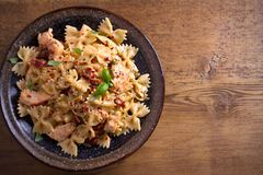 Pasta with chicken, sun dried tomatoes and basil in creamy mozzarella sauce in bowl on wooden table. Overhead, horizontal Stock Photography