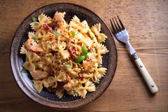 Pasta with chicken, sun dried tomatoes and basil in creamy mozzarella sauce in bowl on wooden table. Overhead, horizontal Stock Images