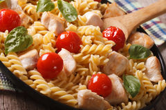 Pasta with chicken, tomato and basil close-up on a plate. horizo Stock Image