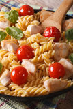 Pasta with chicken, tomato and basil close-up on a plate. Vertic Stock Image