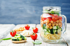 Pasta chickpeas cucumber tomatoes spinach goat cheese salad in a Royalty Free Stock Images