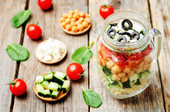 Pasta chickpeas cucumber tomatoes spinach goat cheese salad in a Royalty Free Stock Photography