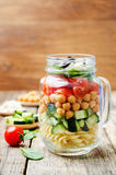 Pasta chickpeas cucumber tomatoes spinach goat cheese salad in a Stock Photos