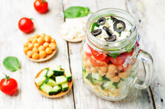 Pasta chickpeas cucumber tomatoes spinach goat cheese salad in a Stock Image
