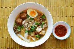Pasta chinesa da farinha de arroz com a carne de porco e as entranhas que cobrem a gema cremosa na sopa Fotos de Stock