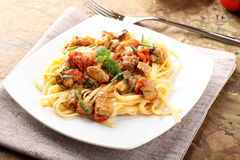 Pasta with chunks of fresh tuna, tomato and mint. On complex background Stock Images