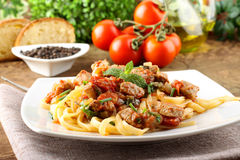Pasta with chunks of fresh tuna, tomato and mint. On complex background Stock Photography