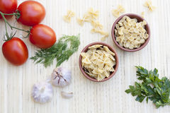 Pasta in a clay pot, green peas, herbs and spices. On light makisu stock photo
