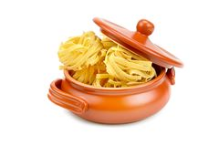 Pasta in a clay pot isolated on white background. Stock Image