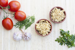Pasta in a clay pot, tomatoes, herbs and spices Stock Image