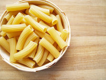 Pasta. Close up basket with pasta on wooden dask Stock Images