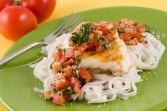 Pasta and cod with tomato pesto. Linguine and grilled cod fillet  toped with tomato pesto Stock Photo