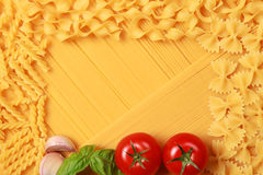 Pasta collection. On a background of spaghettis there are different kind of pasta and tomatos, basil and garlic royalty free stock images