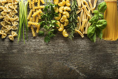 Pasta. Collection with herbs on rustic wooden background Stock Photo