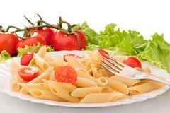 Pasta con i pomodori di ciliegia su una zolla bianca Immagine Stock