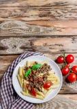 Pasta con i pomodori e la carne su fondo di legno Immagine Stock