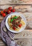 Pasta con i pomodori e la carne su fondo di legno Fotografia Stock Libera da Diritti