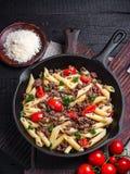 Pasta con i pomodori e la carne su fondo rustico scuro Immagini Stock