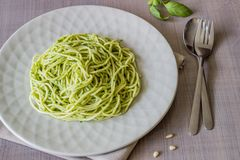 Pasta con la salsa di pesto su un fondo grigio Cucina italiana Alimento vegetariano La dieta fotografia stock