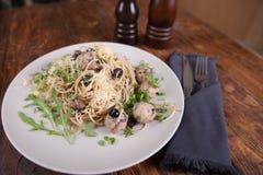 Pasta con le acciughe e le olive nere fotografia stock