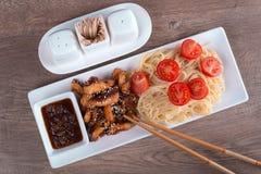 Pasta con salsa acido-dolce e due bastoncini Fotografie Stock