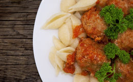 Pasta Conchiglie and meatballs with tomato sauce on rustic woode. N background. Top view Stock Photos