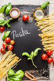 Pasta cooking background with chalkboard, tomatoes, basil and olive oil, top view Royalty Free Stock Photos