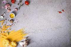 Pasta with cooking ingredients on grey countertop. Italian recipe. View from above, copy space. Royalty Free Stock Photos