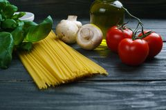 Pasta cooking ingredients. Raw spaghetti, tomatoes, basil, olive. Oil, mushrooms and spices on wooden table, close up. Italian cuisine food background concept royalty free stock images