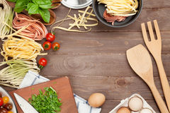 Pasta cooking ingredients and utensils on wooden table Stock Images