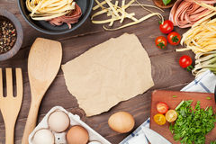 Pasta cooking ingredients and utensils on wooden table Royalty Free Stock Photos