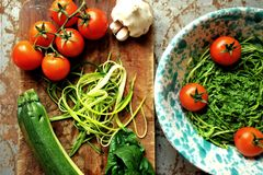 Pasta cruda con il pesto degli spinaci e dello zucchini con i pomodori Immagine Stock Libera da Diritti