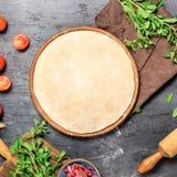 Pasta cruda de la pizza con los ingredientes del sistema para cocinar el pizz vegetariano Foto de archivo libre de regalías