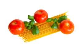 Pasta cruda degli spaghetti con i pomodori freschi e le foglie del basilico isolati Fotografie Stock Libere da Diritti