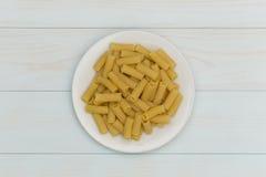 Pasta cruda di tortiglioni in un piatto bianco Fotografia Stock