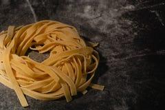 Pasta cruda isolata su un fondo nero con un posto per testo Pasta italiana tradizionale, tagliatelle, tagliatelle Vista superiore fotografia stock libera da diritti