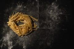 Pasta cruda isolata su un fondo nero con un posto per testo Pasta italiana tradizionale, tagliatelle, tagliatelle Vista superiore immagini stock libere da diritti