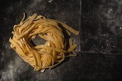 Pasta cruda isolata su un fondo nero con un posto per testo Pasta italiana tradizionale, tagliatelle, tagliatelle Vista superiore fotografie stock libere da diritti