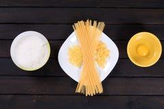 Pasta cruda su una tavola scura, uovo, farina Fotografie Stock
