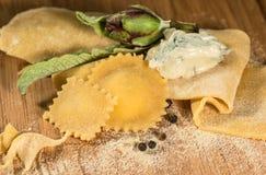 Pasta cruda y raviolis hechos en casa italianos con el queso de queso Gorgonzola, la alcachofa fresca y algunos granos de la pimi Foto de archivo libre de regalías