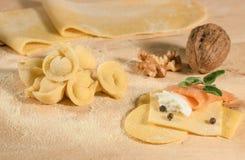 Pasta cruda y tortellini hecho en casa italiano, abierto y cerrado, llenados de queso del ricotta, del salmón ahumado, de las hie Foto de archivo