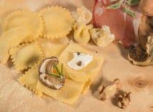Pasta cruda y tortellini y raviolis hechos en casa italianos, abierto y cerrado, llenados de queso del ricotta, de setas y de hie Imagen de archivo