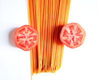 Spaghetti and cut tomatoes closeup. Spaghetti and chopped tomatoes closeup on white background Royalty Free Stock Photo