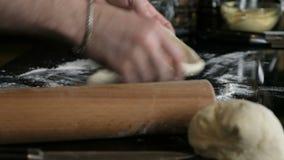 Pasta d'impastamento del panettiere in farina sulla tavola stock footage